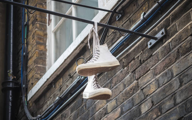 Shoes dangling outside a brick wall at Brick Lane market in London stock photo