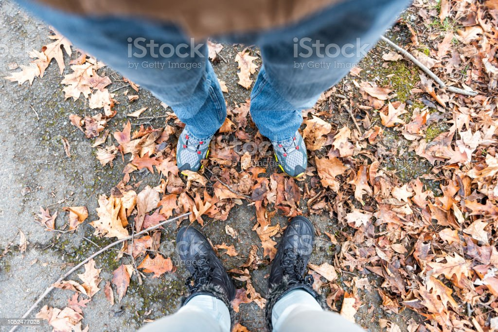 Shoes, fallen autumn brown orange many leaves on ground with woman...