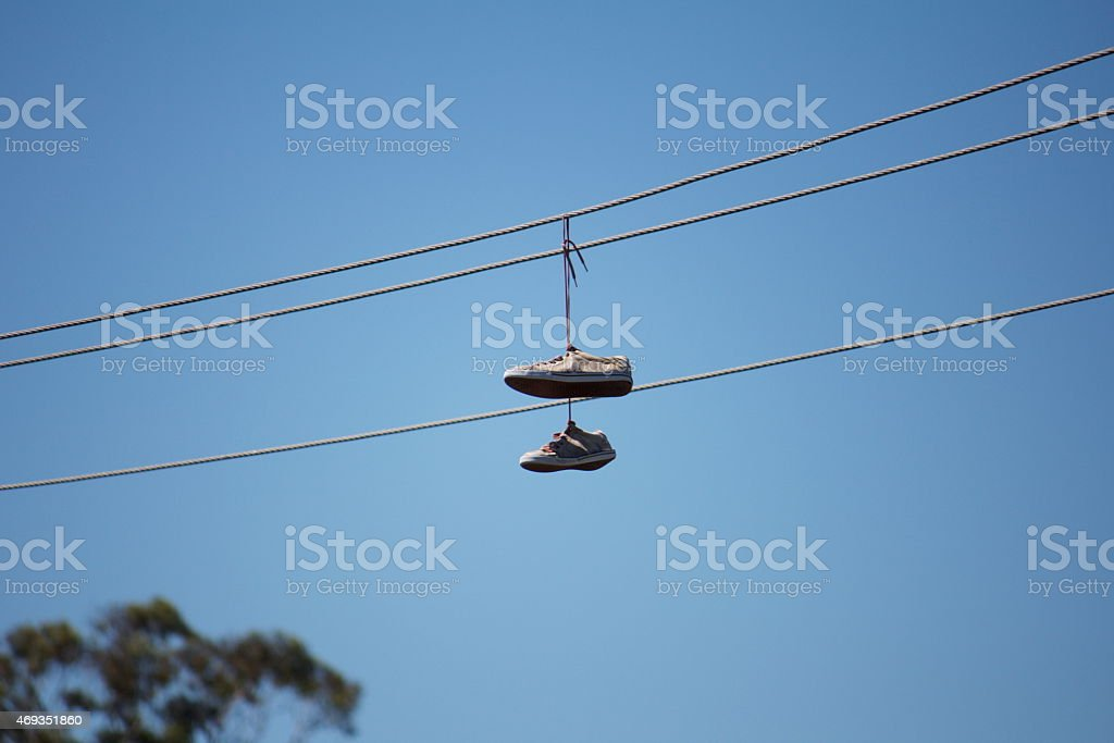 Shoes hang from a telephone wire.