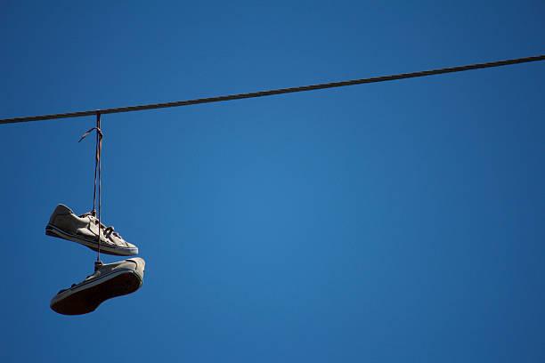 schuhe hängen auf einem telefon wire - kabelschuhe stock-fotos und bilder