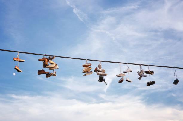 schuhe, die an ein elektrisches kabel hängen - kabelschuhe stock-fotos und bilder