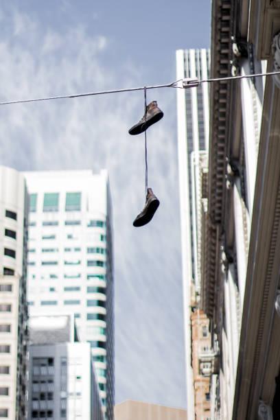 schuhe hängen auf stromleitung in der innenstadt von san francisco - kabelschuhe stock-fotos und bilder