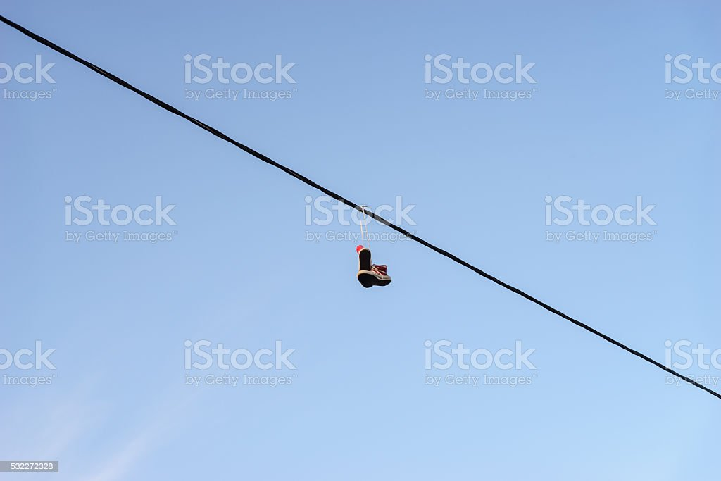 Old pair of shoes hanging on telephone wire against blue sky, life...