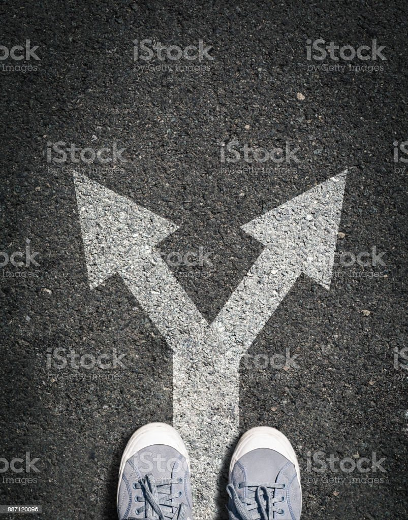 shoes on asphalt road with two directions sign, concept is making choice and makin decsion stock photo