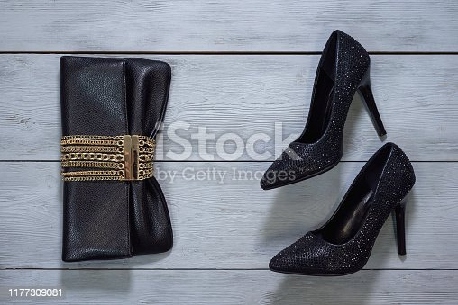 Black high heels shoes and clutch bag on wooden floor background.