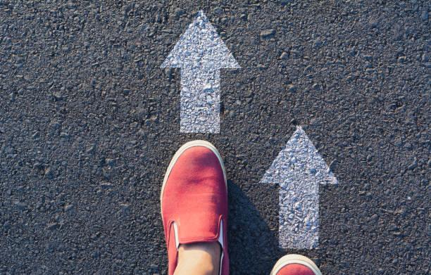 Schuhe stehen an der Kreuzung und entscheiden, welchen Weg zu gehen. Möglichkeiten, das Konzept auszuwählen. – Foto
