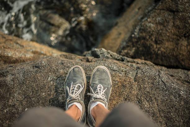 buty stojące na skraju klifu nad oceanem - klif zdjęcia i obrazy z banku zdjęć