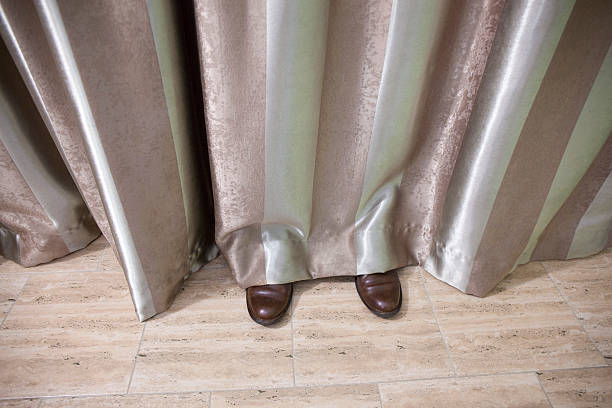 Shoes Visible Behind and Under Curtains - foto de stock