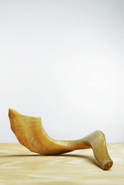 Shofar on wooden table in front of white wall stock photo