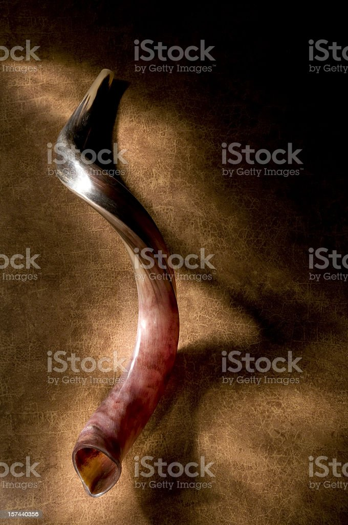 Shofar with shadow, brown background and a glow of light. stock photo