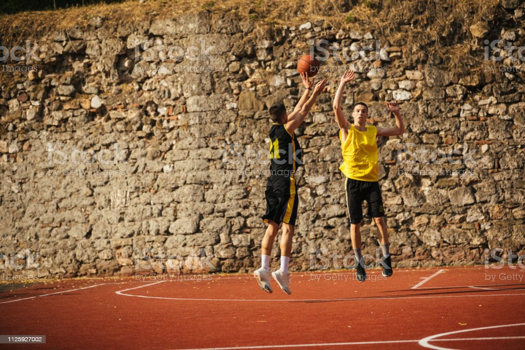 Basketball player in black uniform jumping, shooting for three points...