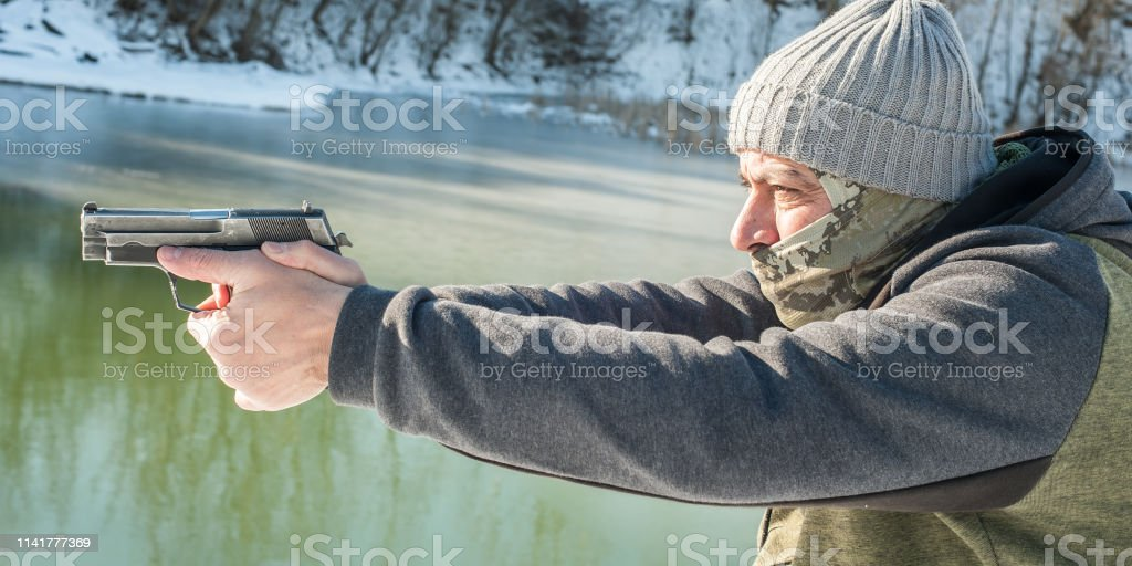 Detail view of shooter holding gun in hand and shooting on the winter...