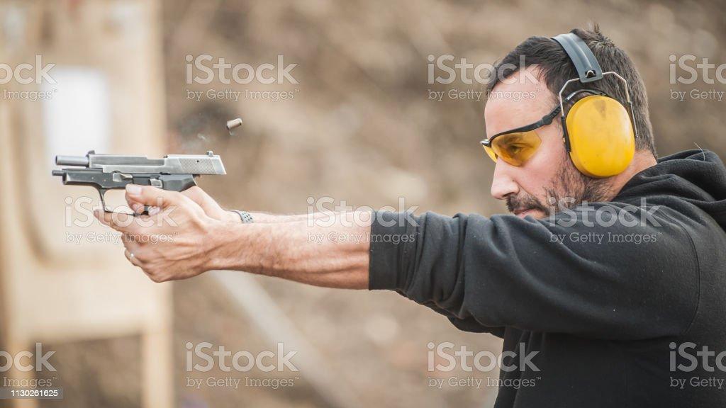 Shooter Holding Gun And Training Tactical Shooting Closeup