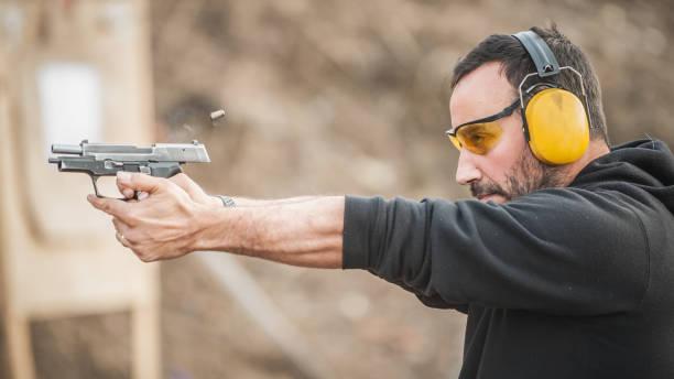 shooter houden pistool en opleiding tactische schieten. close-up-detailweergave - gun shooting stockfoto's en -beelden