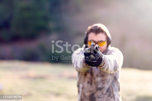 Shooter holding gun in hand and shooting. Close-up detail