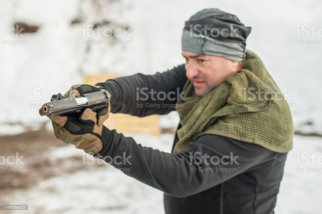 Detail view of shooter holding gun in hand and shooting, close up....