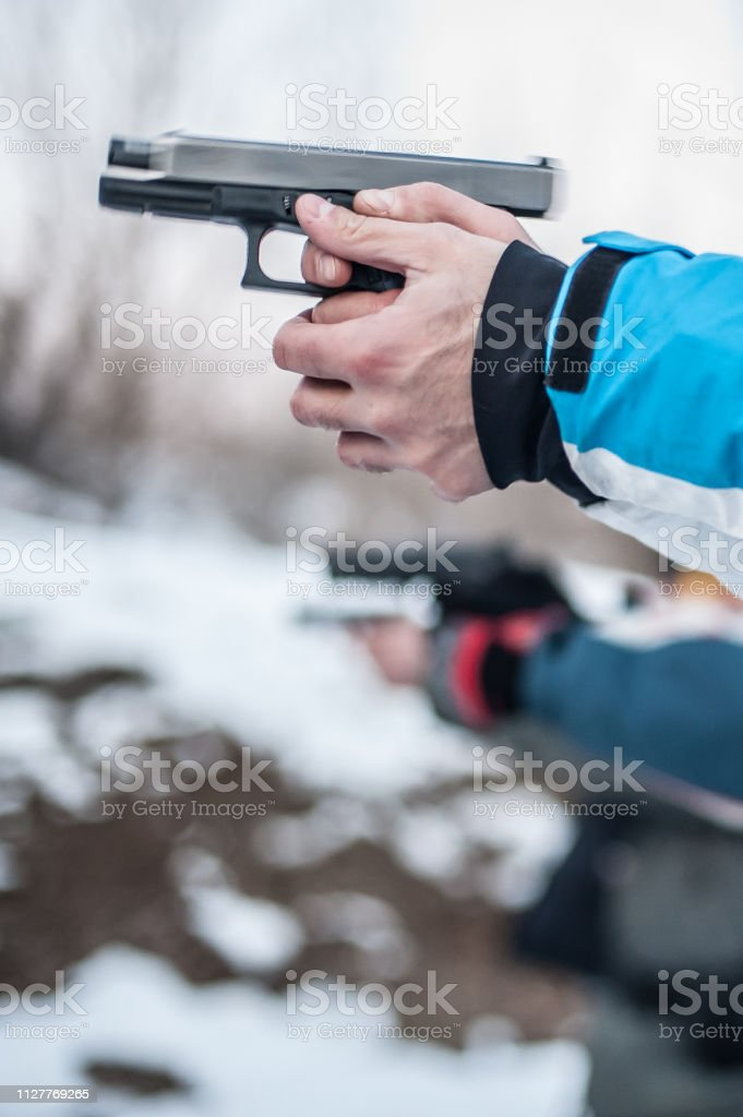 Detail view of shooter in row group of people hold gun and shooting...