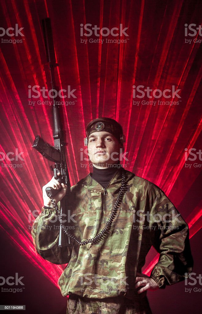The manly young man in military uniform posing with a laser gun in...
