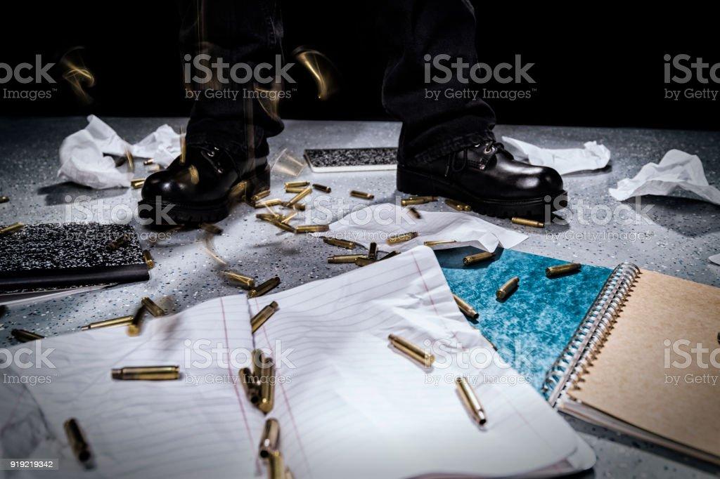 Shooter's feet as bullet casings rain down on school notebooks. stock photo
