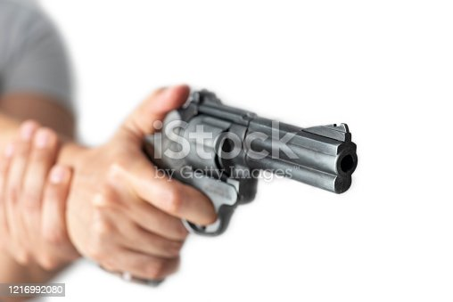 Unrecognizable persons hand  is holding a gun with one hand in front of pure white background.