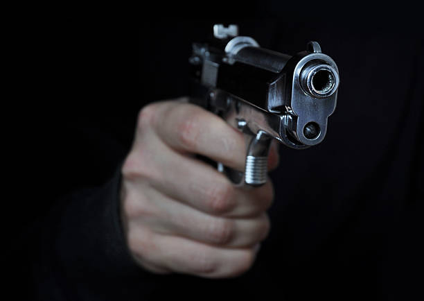 Shooting a gun Shooting a gun in night pistol stock pictures, royalty-free photos & images