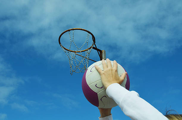 shooting a netball goal - netball stockfoto's en -beelden