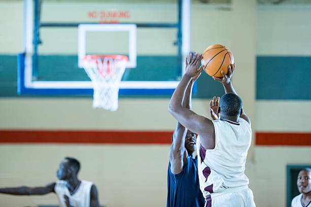 Shooting a Three Pointer A group of college age men are playing a basketball game together at an indoor gym. jump shot stock pictures, royalty-free photos & images
