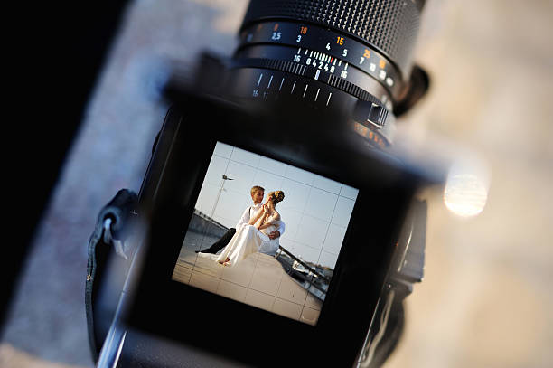 shooting a wedding with an oldschool camera - wedding photography and videography stock-fotos und bilder