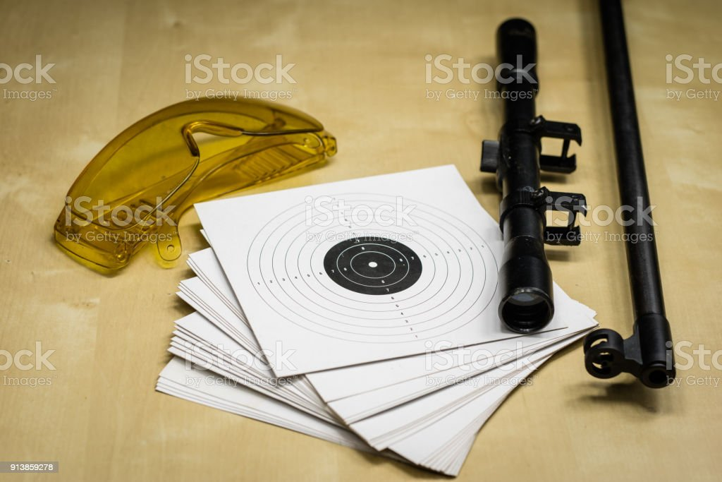 Shooting accessories on a wooden table in a shooting range. Shield and projectiles for pneumatic weapons before shooting. Black background. stock photo