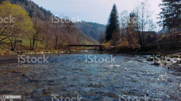 Photo of Shooting along the flowing water of a mountain river to the small bridge.