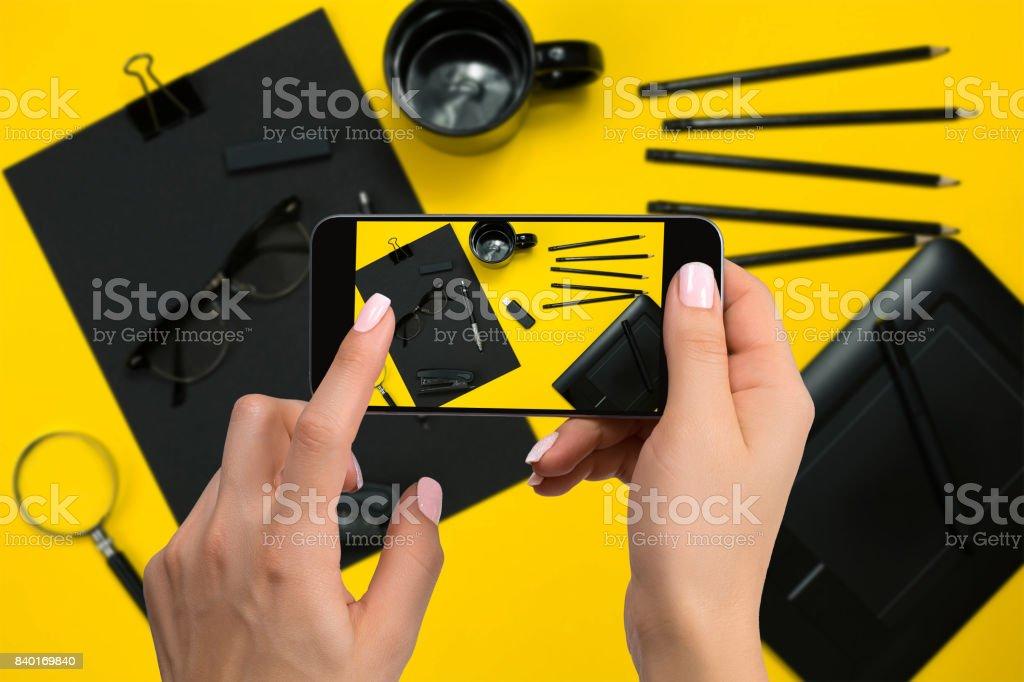 Shooting black stationery on phone's camera. Stationery on yellow background stock photo