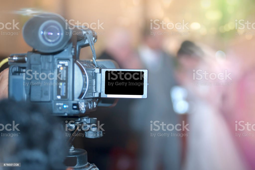 shooting bride and groom with video camera in wedding ceremony, focus at camera. stock photo