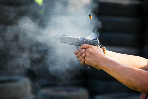 Shooting from a pistol. Reloading the gun. The man is aiming at the target