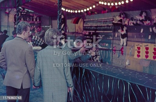 Berlin (West), Germany, 1967. Visitors and customers (shooter), in front of a shooting gallery on a fairground.