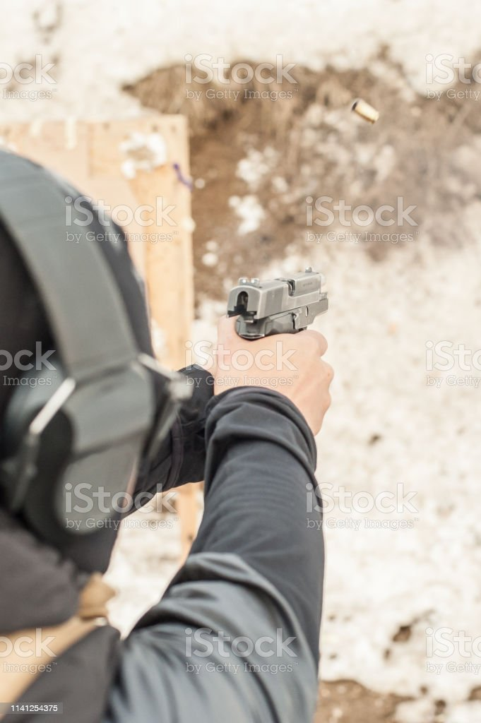 Detail back view of shooter holding gun in hand and shooting on...