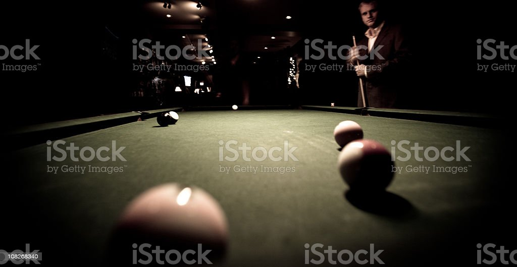 Shooting pool at a bar - contemplating next shot stock photo