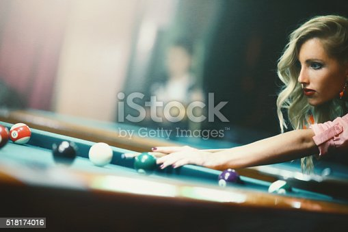 Closeup side view of lae 20's blond woman shooting some pool on weekend night. She's with her friends that are out of the frame at the moment, having few games and drinks before going out.