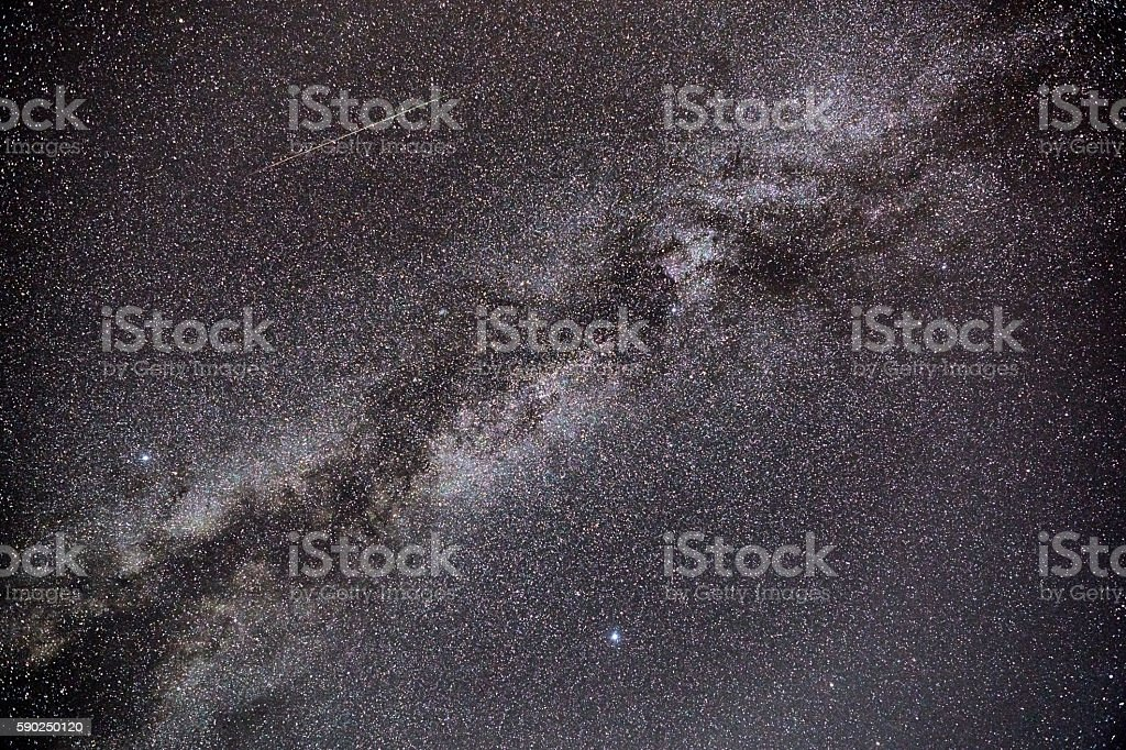 A Perseid meteor streaks across the sky, in parallel with the Milky...