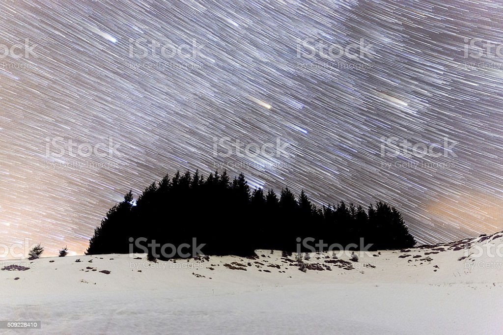 The Milky Way over the winter mountain landscape with s silhouette of...
