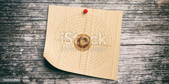 1048647890 istock photo Shooting target on recycling carton paper, wooden wall background. 3d illustration 1043434564