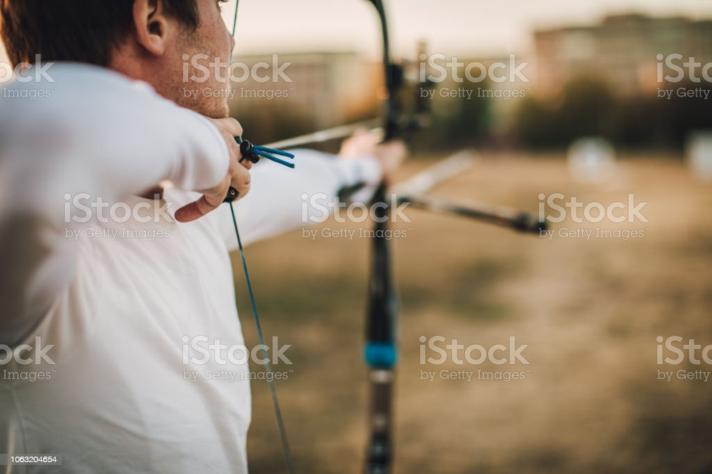 Young man practicing archery outdoors