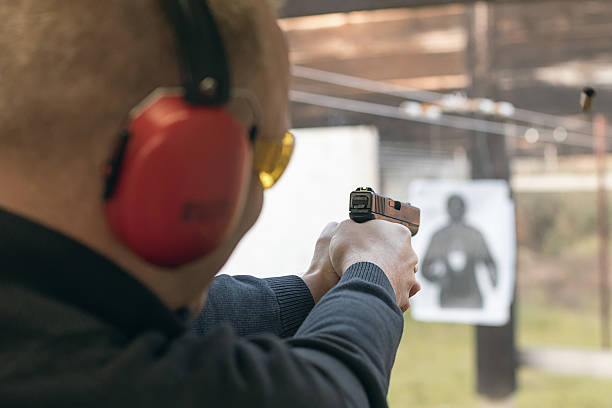 Shooting with a pistol. Man aiming pistol in shooting range. stock photo
