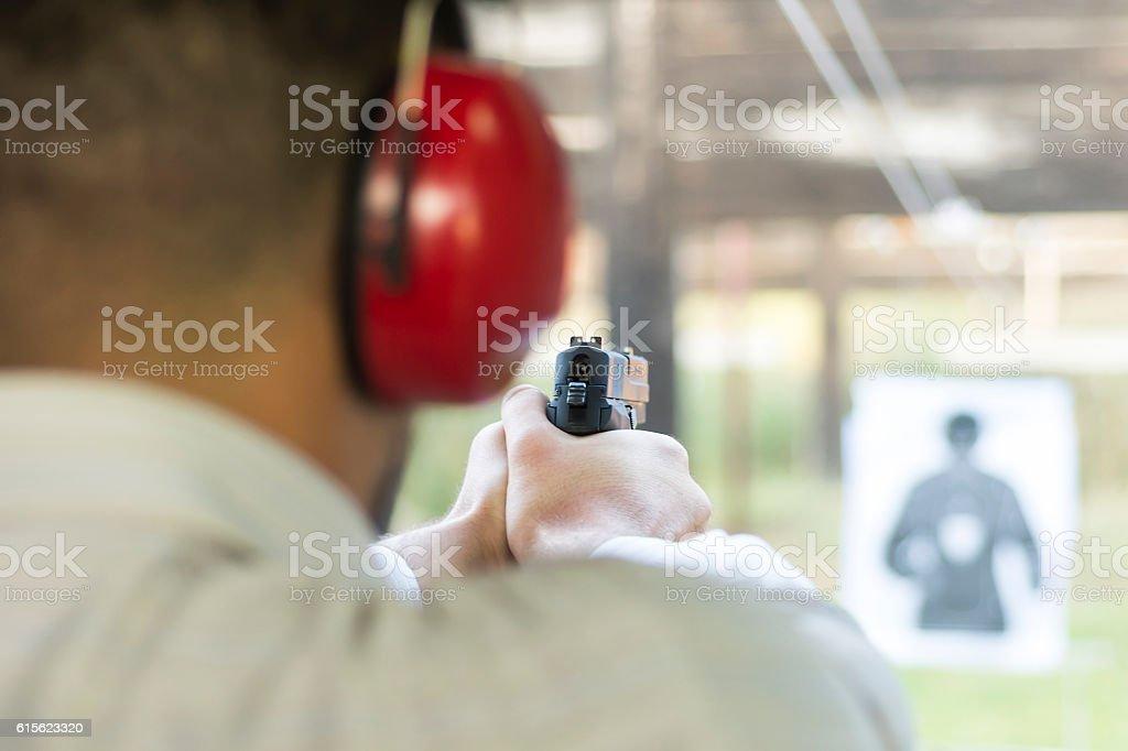 Shooting with Gun at Target in Shooting Range - foto de acervo