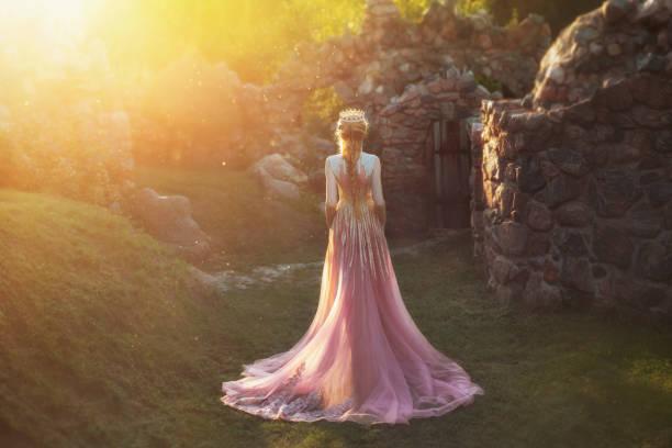 後ろから、顔なしで撮影。ブロンドの髪と王冠素晴らしい姫です。金の装飾品と長い列車の素晴らしい光ピンクのドレスを着ています。女王が太陽の光の庭で散歩します。 - プリンセス ストックフォトと画像