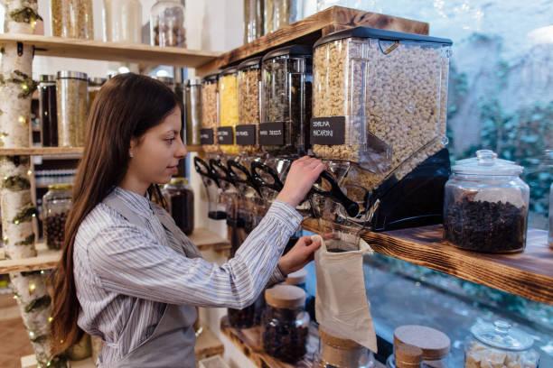 shop assistant filling reusable bag with dried pasta in organic grocery store. - rifiuti zero foto e immagini stock