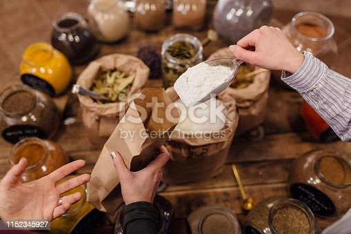 Zero waste shopping - woman buying fresh herbs and spices at package free grocery store.