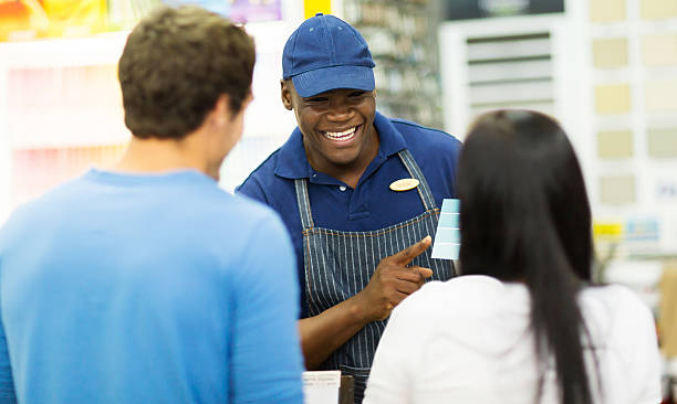shop assistant helping couple choose paint color at hardware store stock photo