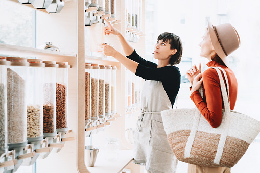 istock Shop assistant helping customer in bulk food store. 1190360683