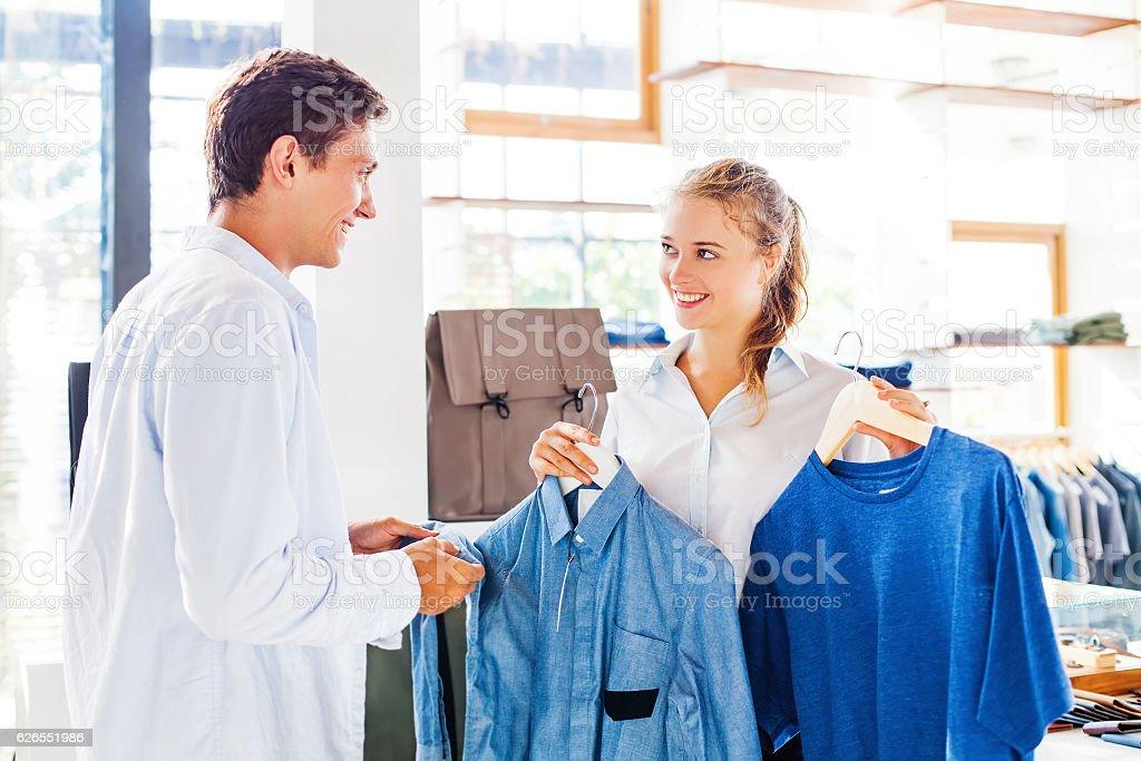 shop assistant helping to choose clothes photo libre de droits
