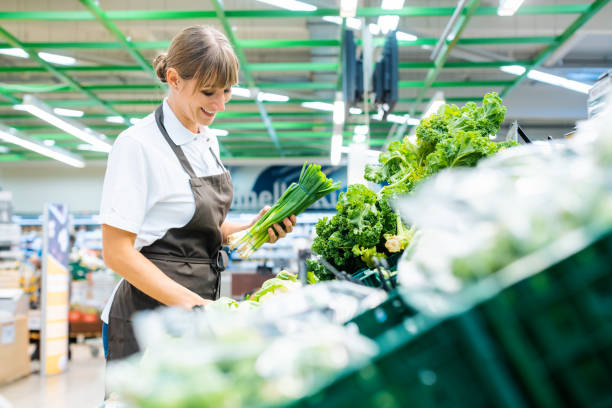 Shop assistant in supermarket re-stocking fresh vegetables stock photo